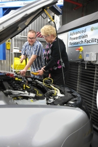 Argonne researchers Dave Shimcoski and Ann Schlenker measure the electrical change of a hybrid vehicle in the Advanced Powertrain Research Facility's Environmental Test Cell.